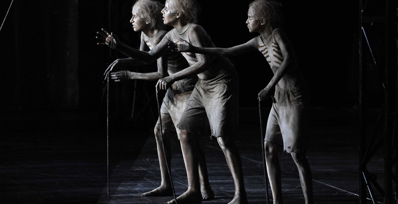Three skeletons with walking sticks holding out their hands in ENO's The Magic Flute