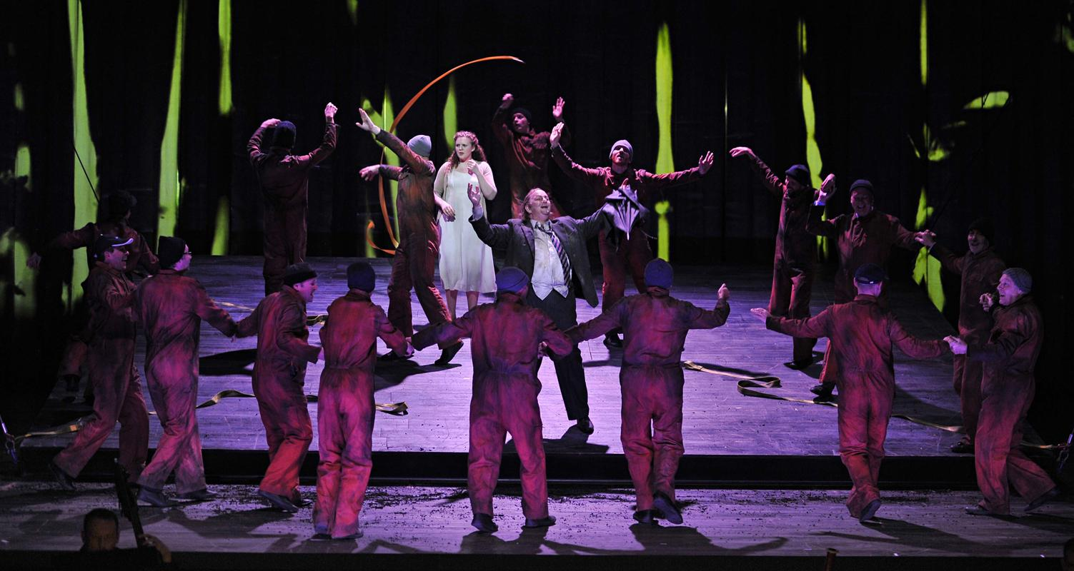 Man and woman surrounded by group in orange jumpsuits in ENO's The Magic Flute