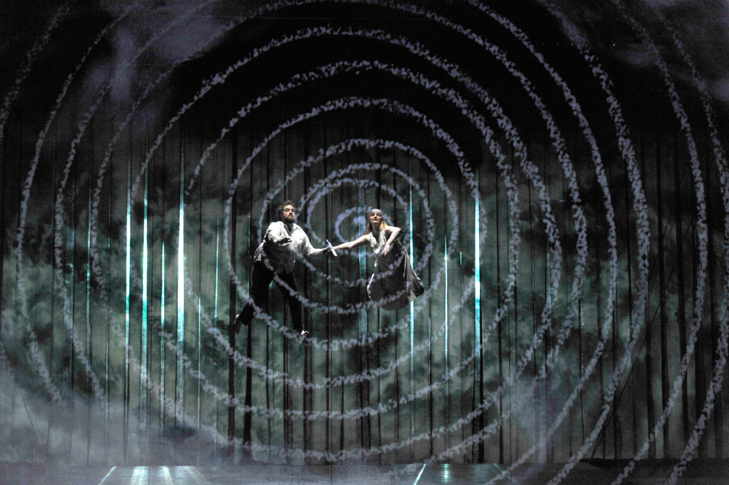 A man and woman suspended in mid-air above the stage in ENO's The Magic Flute