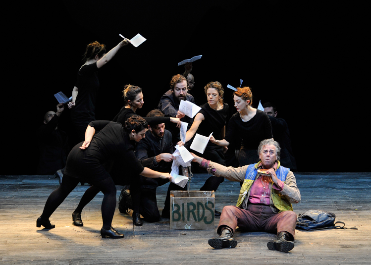 Group of people wearing black placing white pages into a box labelled 'birds' in ENO's The Magic Flute