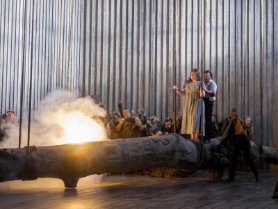norma marjorie owens and peter auty walking on a log with fire onstage with eno chorus