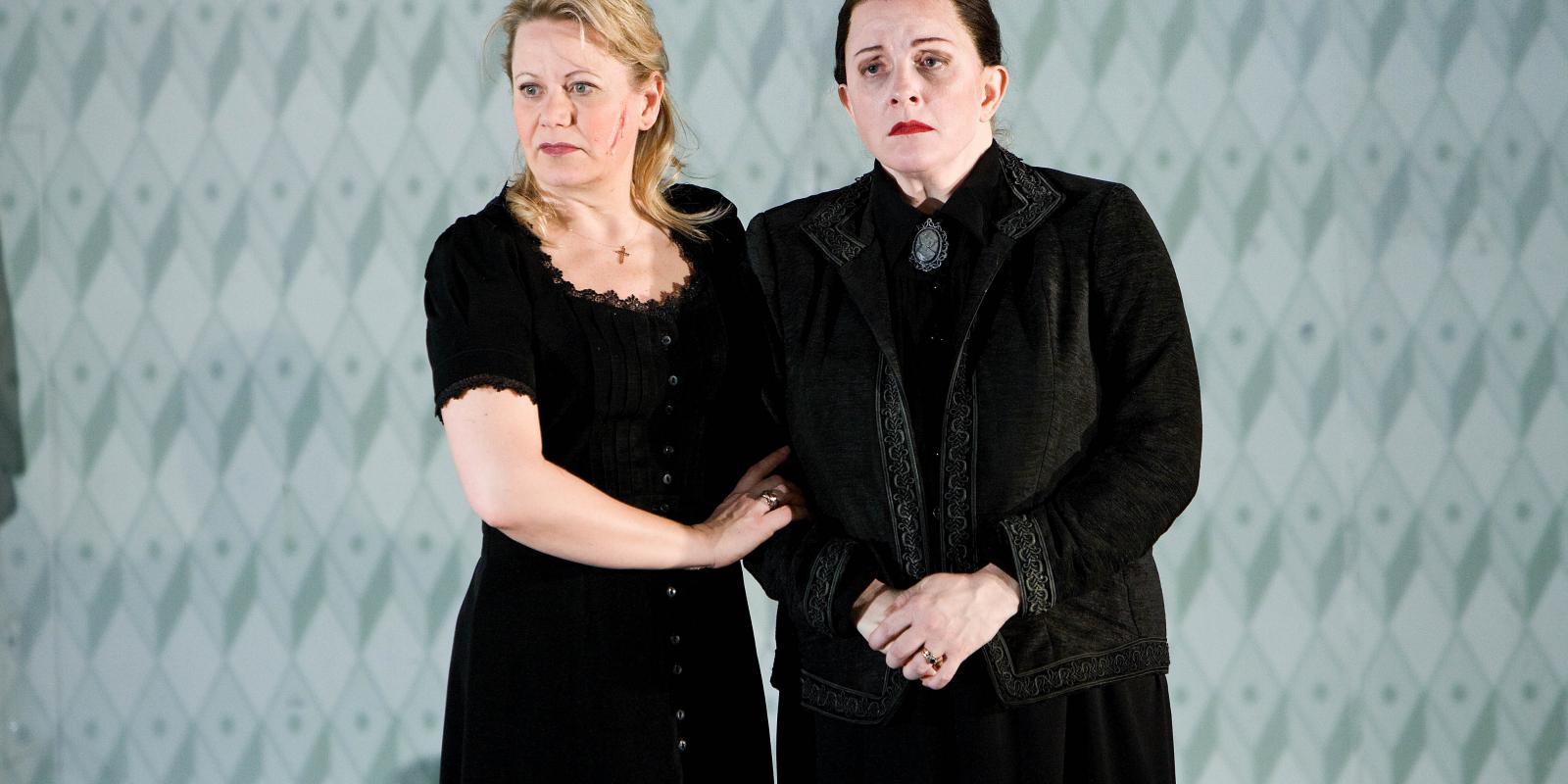 two women in grieving close interlocking arms in Jenufa