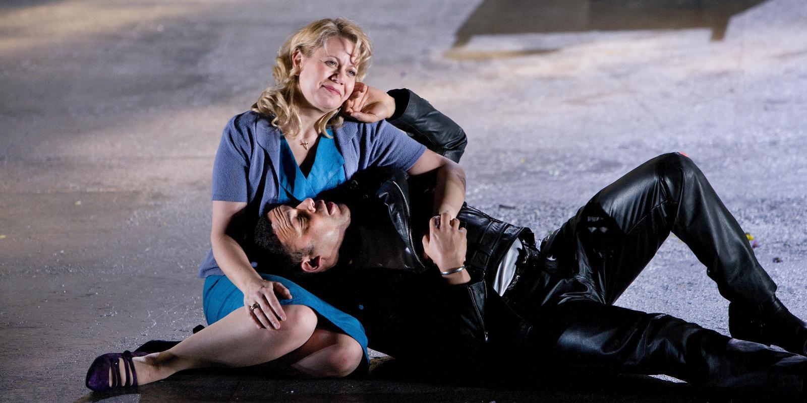 man lying on woman in blue dress in Jenufa