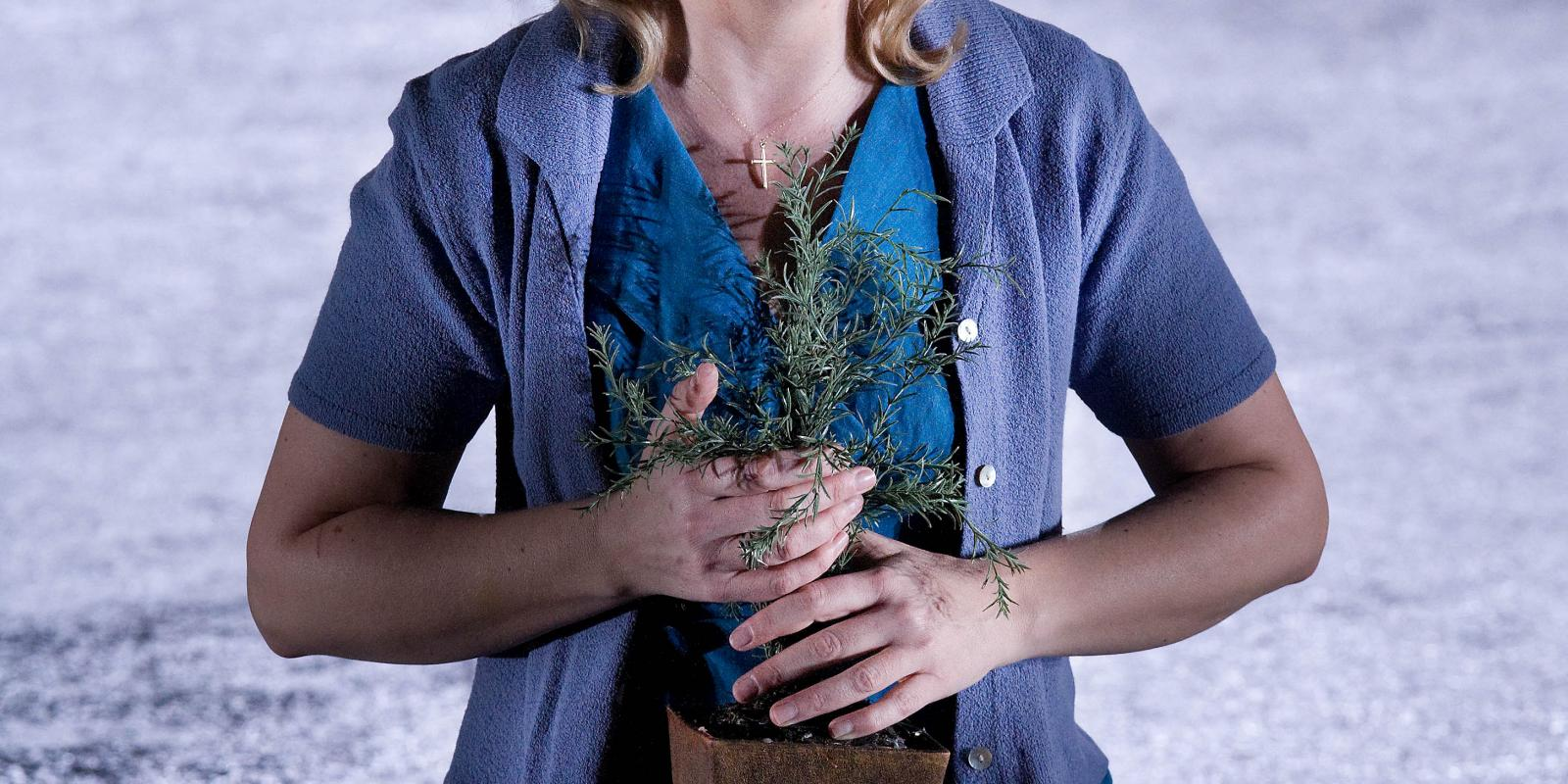 Woman in blue outfit holding a houseplant in ENO's Jenufa