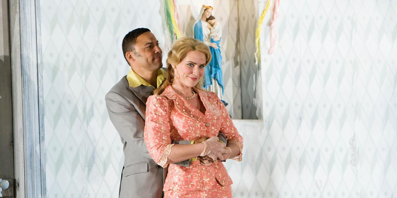 Man in grey suit with arms wrapped around a woman in a pink outfit in ENO's Jenufa