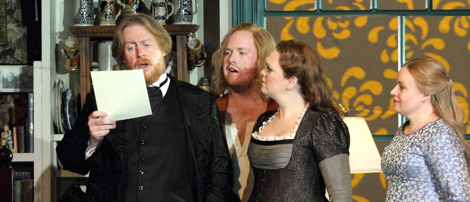 ENO's The Mastersingers of Nuremberg- Iain Paterson as Hans Sachs, Wendy Bryn Harmer as Eva, Nicky Spence as David and Madeleine Shaw as Magdalene. Photo by Catherine Ashmore.
