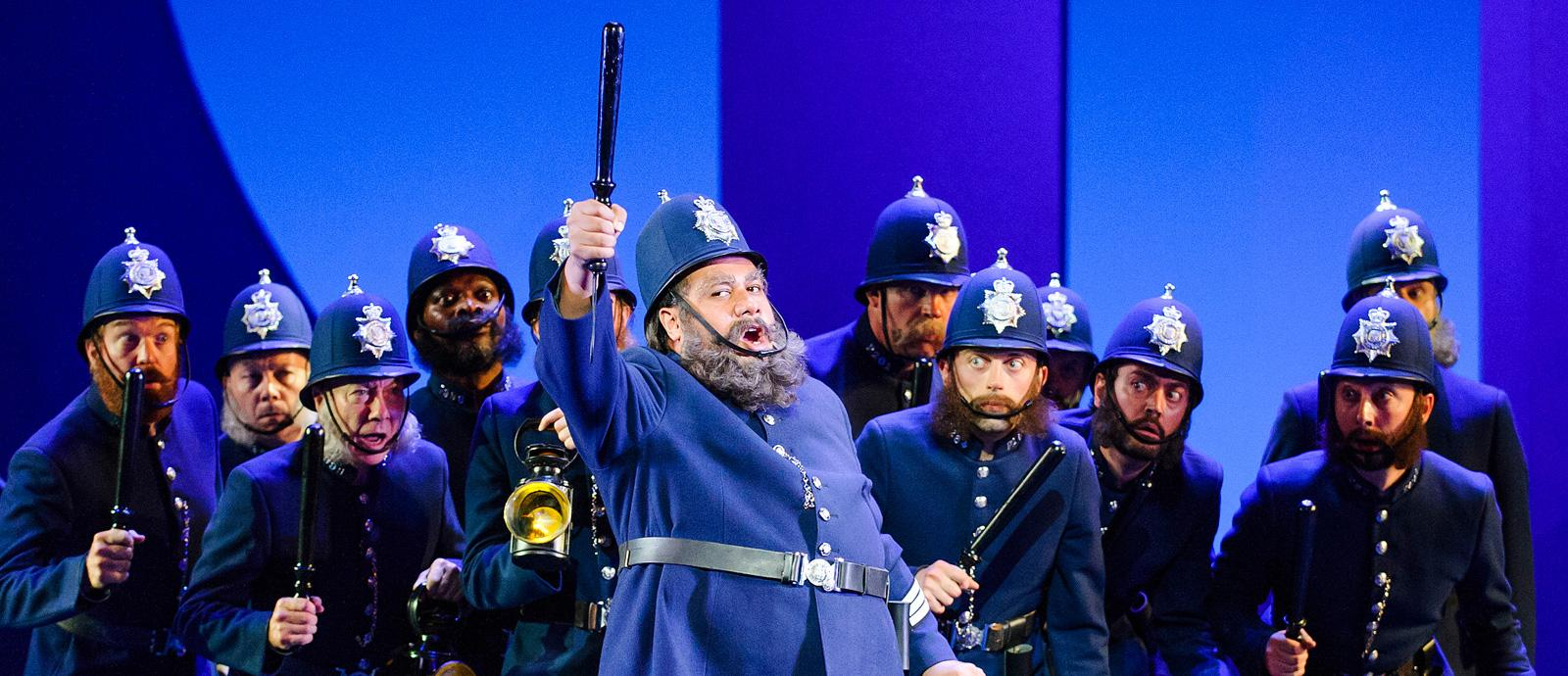 ENO's The Pirates of Penzance - Jonathan Lemalu as Sergeant of Police and Company. Photo by Tristram Kenton
