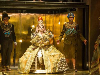 characters from akhnaten on stage in gold outfits