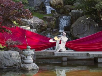 character from madam butterfly by a lake wrapped in big red ribbon