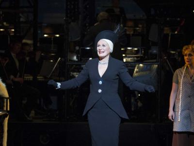 glenn close in a black suit performing on stage