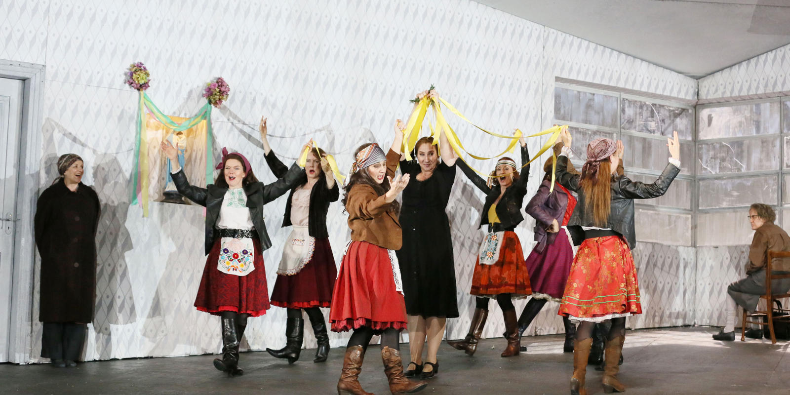 Group of women singing and dancing while holding yellow ribbon in ENO's Jenufa