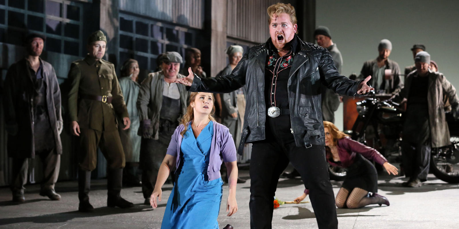 Man with ginger hair in leather jacket sings while group watches in ENO's Jenufa
