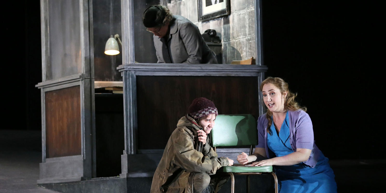 Woman in a blue dress and cardigan sitting with a homeless woman in ENO's Jenufa