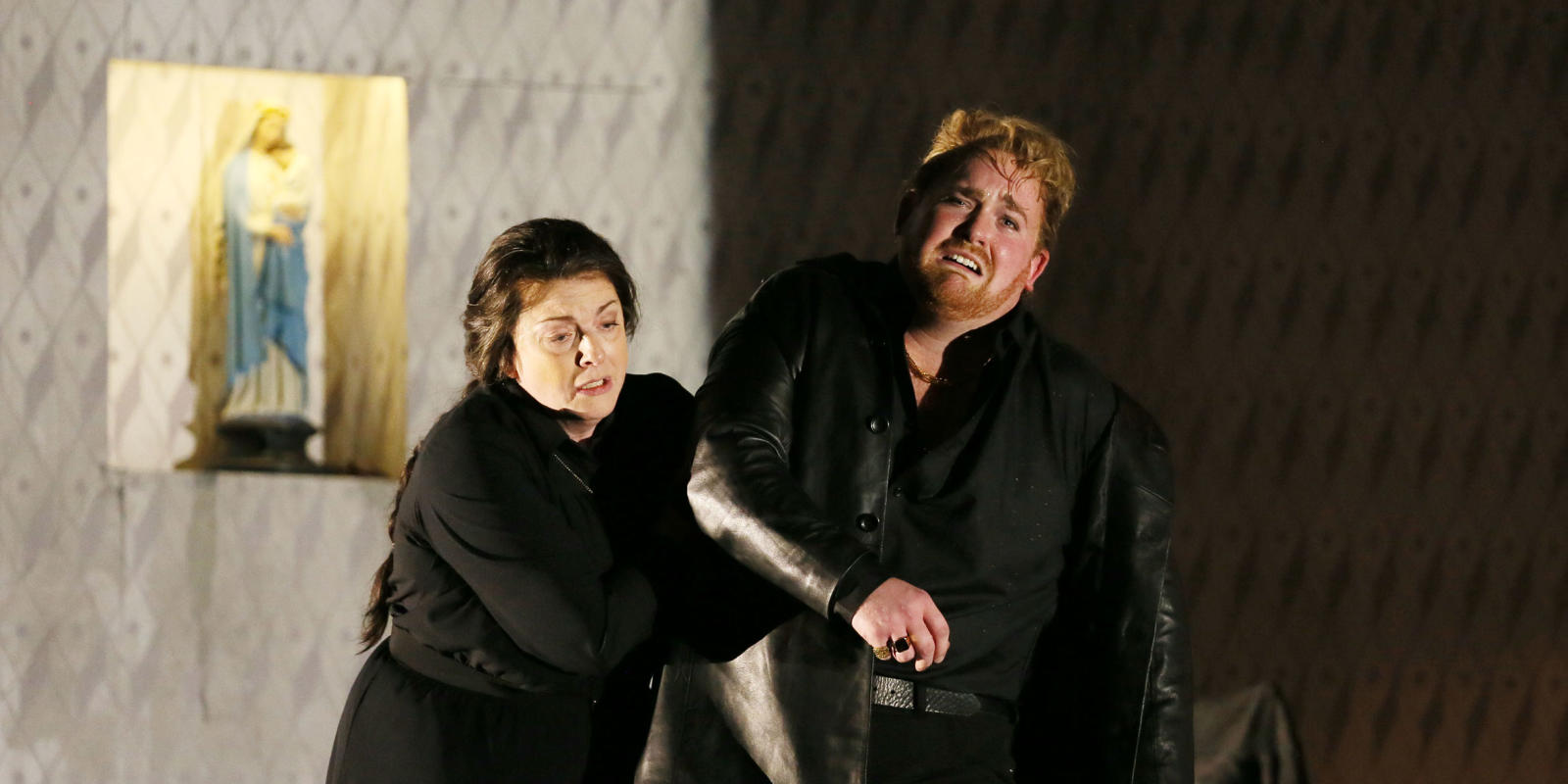 Visibly distraught man with ginger hair in a black coat being ushered by a woman in ENO's Jenufa