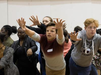group of actors rehearsing with arms outstretched