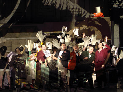actors on stage suits holding up big paper hands in ENO's Lulu