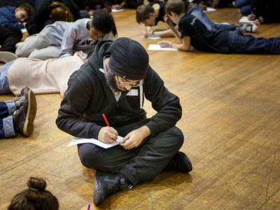 young man writes in a notebook whilst backstage at a theatre