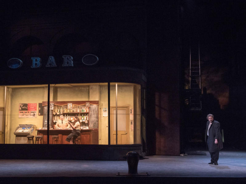 Characters from Rigoletto stood outside a bar