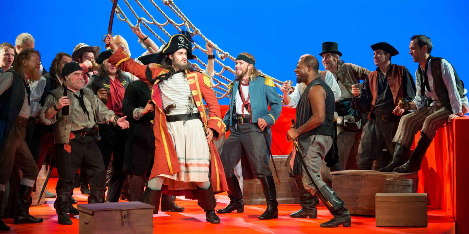 ENO's The Pirates of Penzance - Ashley Riches as The Pirate King, Johnny Herford as Samuel and ENO Chorus. Photo by Tom Bowles