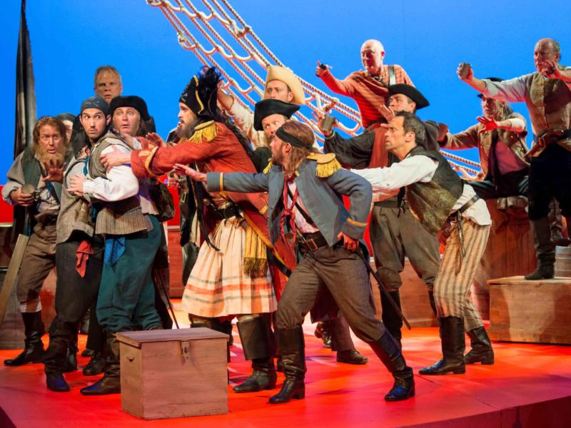 ENO's The Pirates of Penzance - David Webb as Frederic, Ashley Riches as The Pirate King, Johnny Herford as Samuel and ENO Chorus. Photo by Tom Bowles