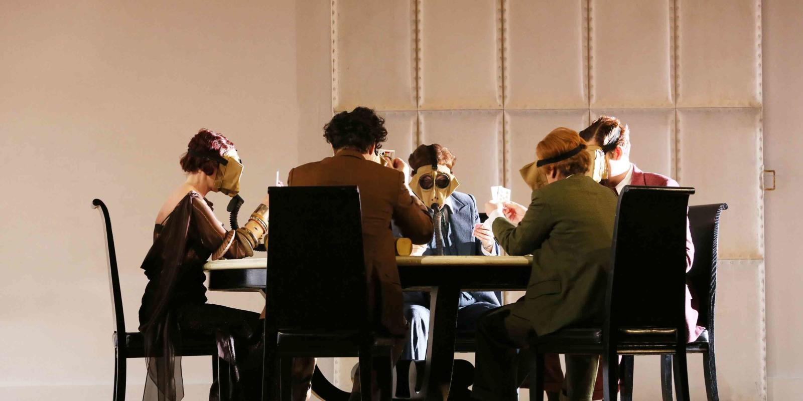 The Partenope cast playing cards at a table during ENO's 2017 production