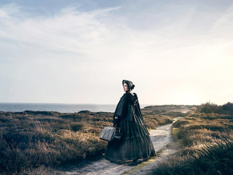 The Governess wearing a bonnet stood on a sandy dune next to the sea