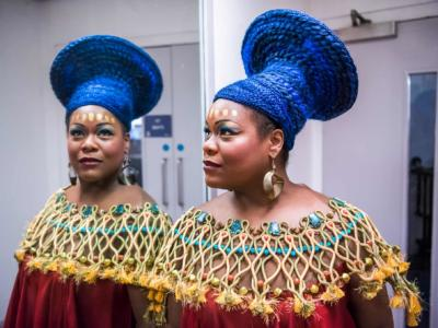 woman performing in aida standing by a mirror backstage in full African makeup and costume