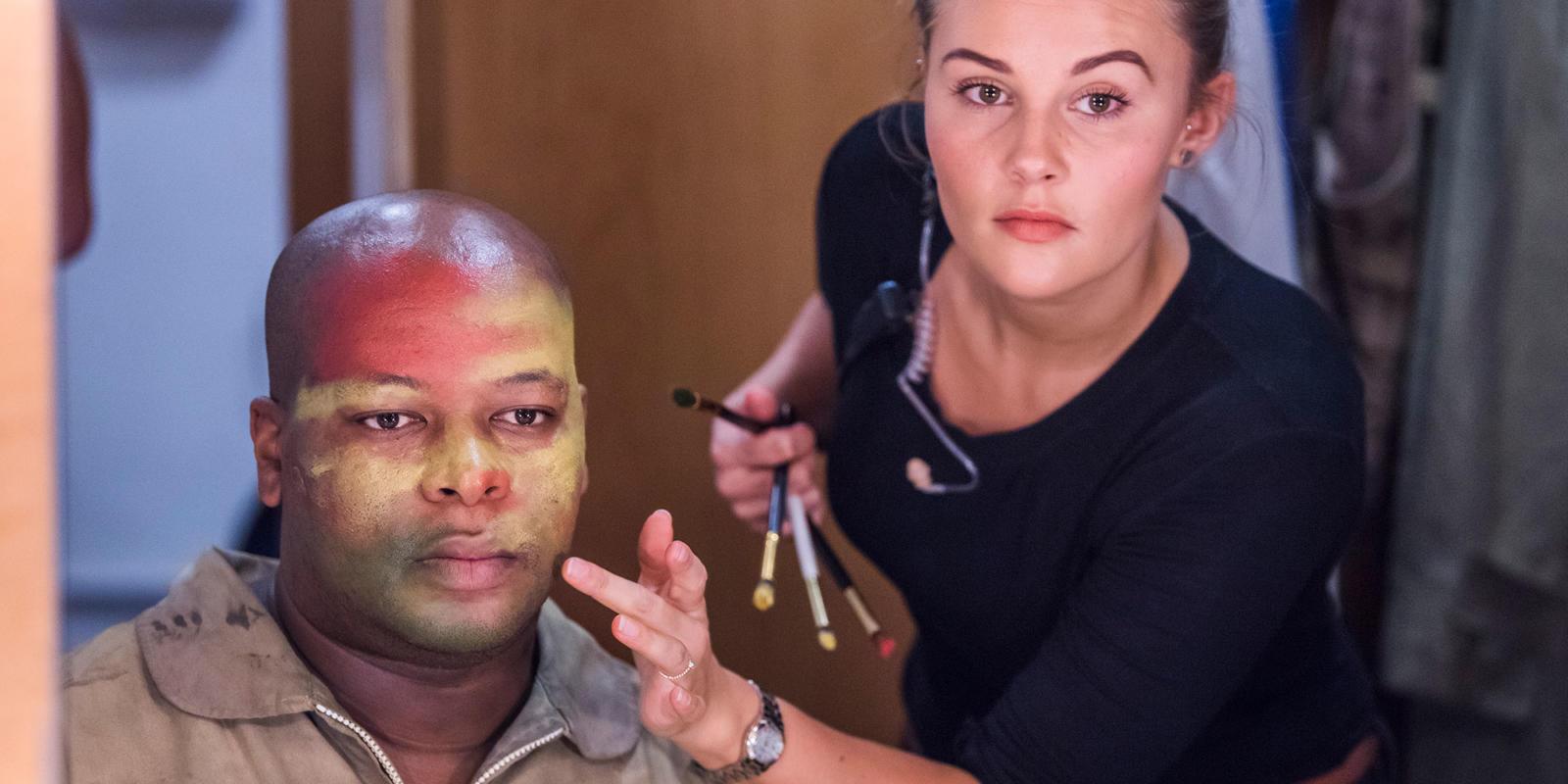 Musa Ngqungwana, who sings as war-king, Amonasro, has his war paint applied by makeup artist Taylor Rands (c) Tristam Kenton
