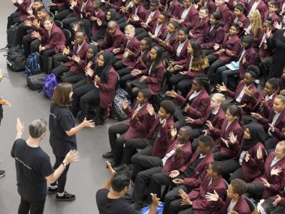 aerial shot of woman speaking to hall full of schoolchildren