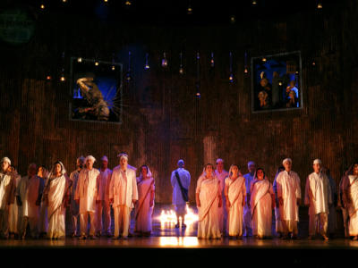 satyagraha cast performing on stage next to flame torches