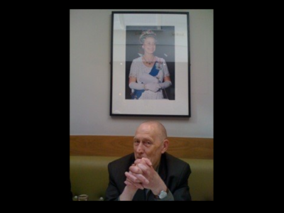 tony browne sat in front of framed photo of the queen