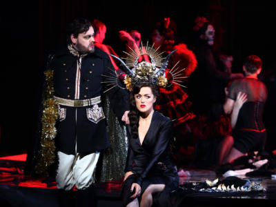 Violetta wearing a black dress and headpiece glancing to the side of the stage with Baron Douphol standing next to her