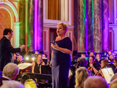 Susan Bullock singing to guests in front of an orchestra at ENO's Gala Dinner