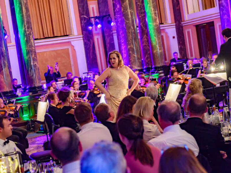 Woman singing to guests in front of an orchestra at ENO's Gala Dinner