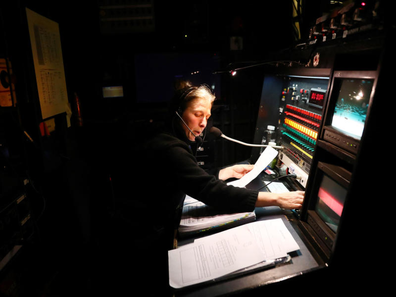 Soundman wearing a microphone at a sound desk backstage of ENO