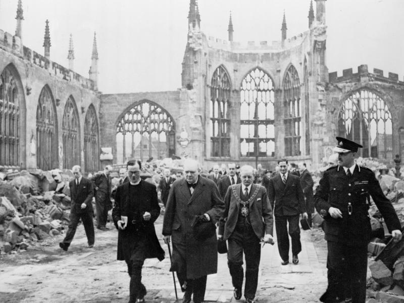 Winston Churchill walking through the ruined nave of Coventry Cathedral, England, after it was severely damaged in the Coventry Blitz of 14–15th November 1940