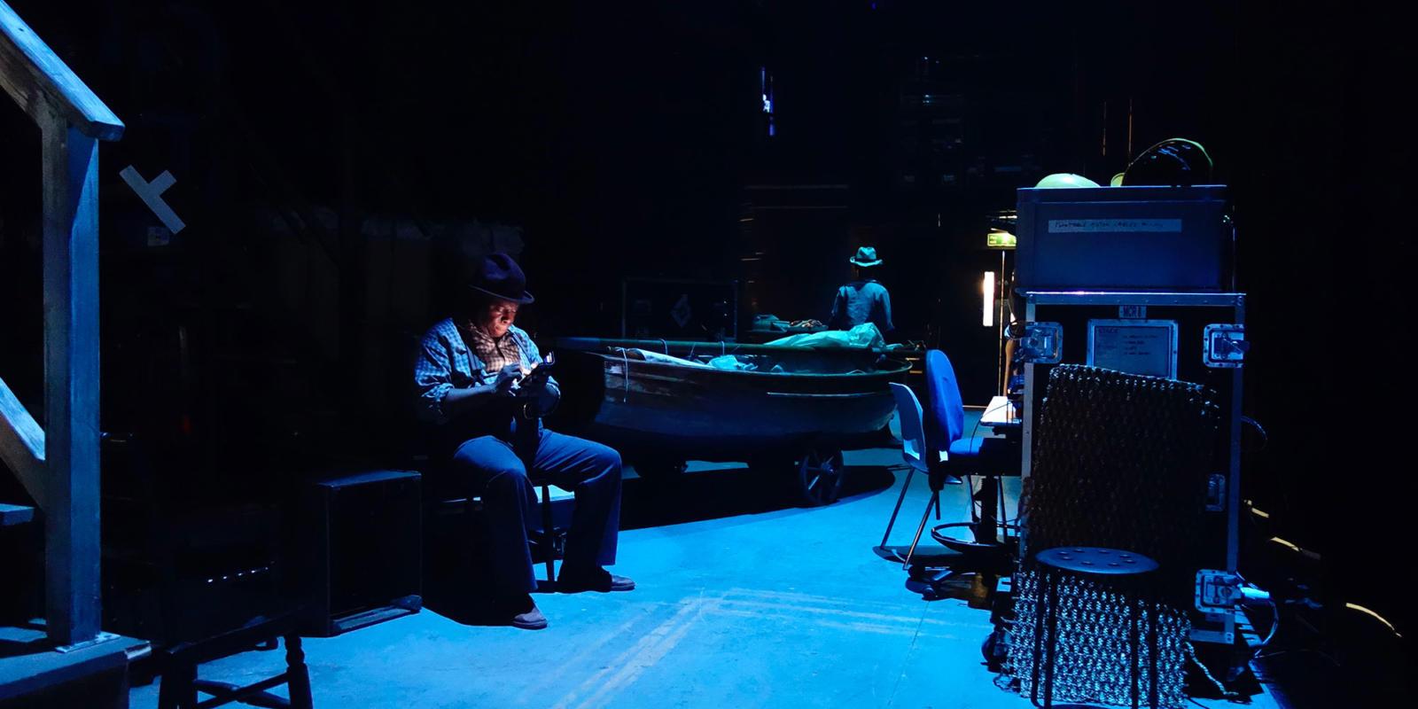 Ensemble member Calvin Lee checks his phone in the wings