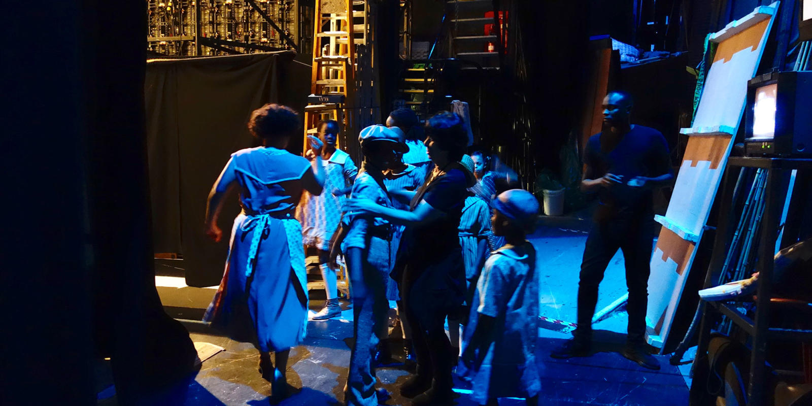 Members of the Children's Chorus play with one another in the wings