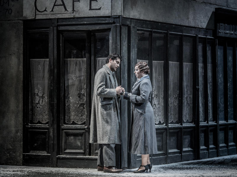 Mimi and Rodolfo in La Bohème clutching each other's hands in front of a shop
