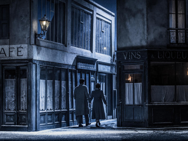 Main roles from La Bohème walking down a small dark alleyway holding hands