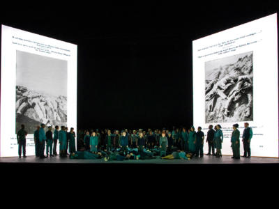Ensemble of War Requiem stood on stage with projections of a German anti-war pamphlet behind them