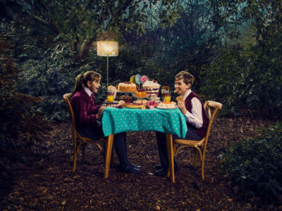 A young Hansel and Gretel having a tea party in a woodland