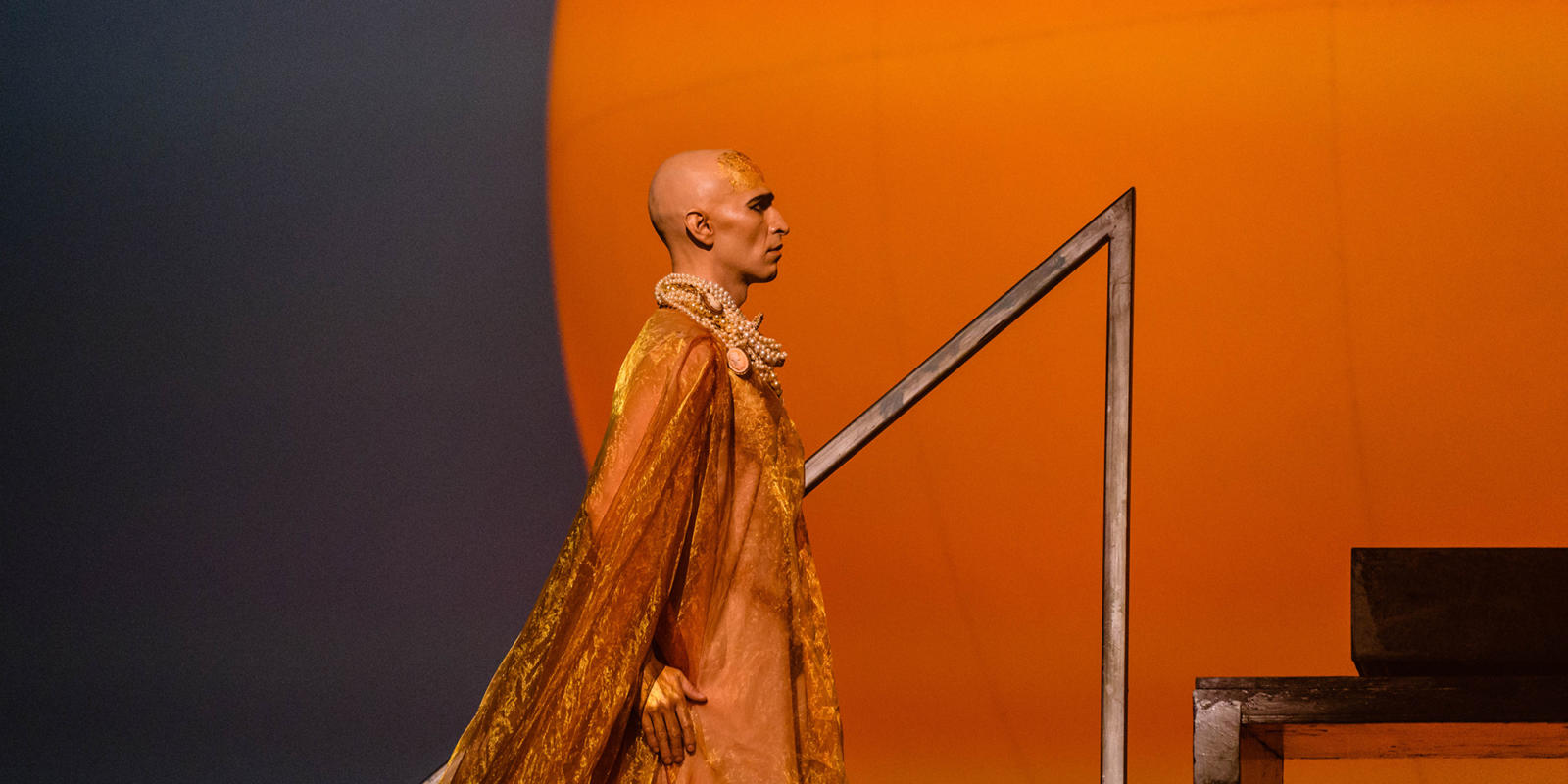 Anthony Roth Costanzo in the title role of Akhaten wearing a velvet orange cape in front of the bright orange sun