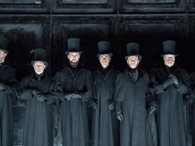 Male cast members from Jack the Ripper: The Women of Whitechapel dressed in black coats and top hats looking earnest