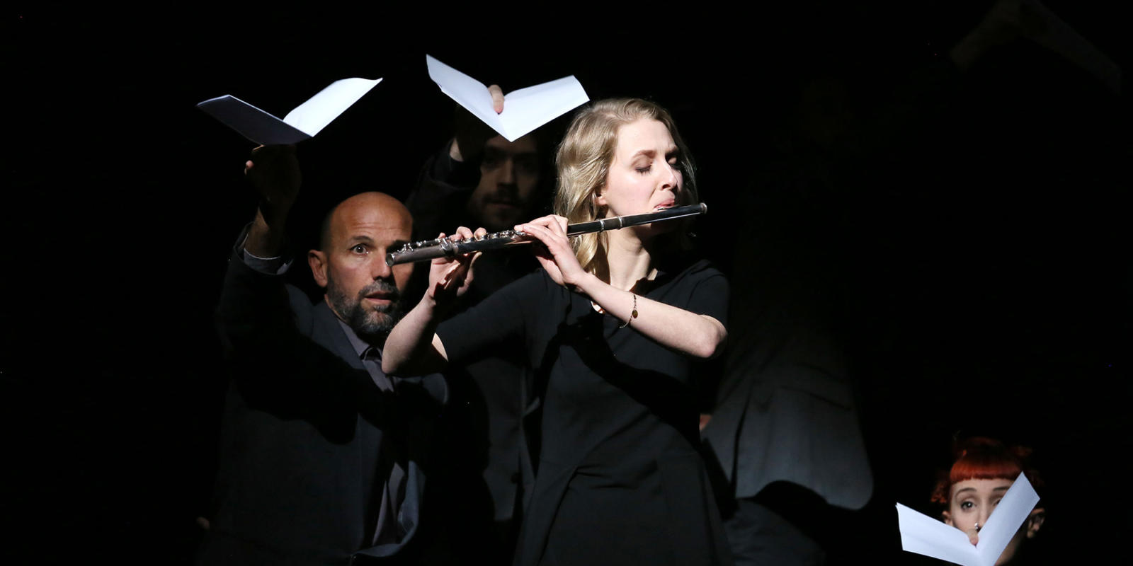 Blonde woman playing the flute on stage