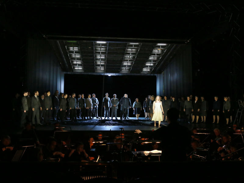 Cast members of The Magic Flute stood on a dimly lit stage with the orchestra playing in front
