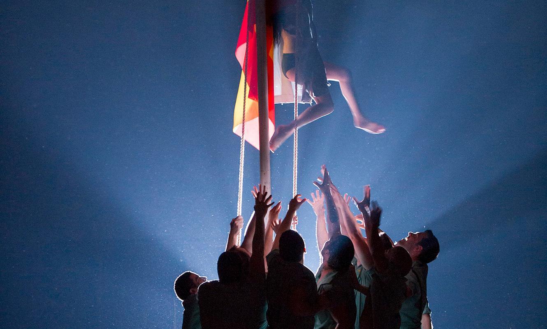 ENO Carmen 2015: Members of the ensemble raise the Spanish flag (c) Alastair Muir