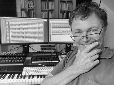 Ian Dearden by his keyboard and computer monitors