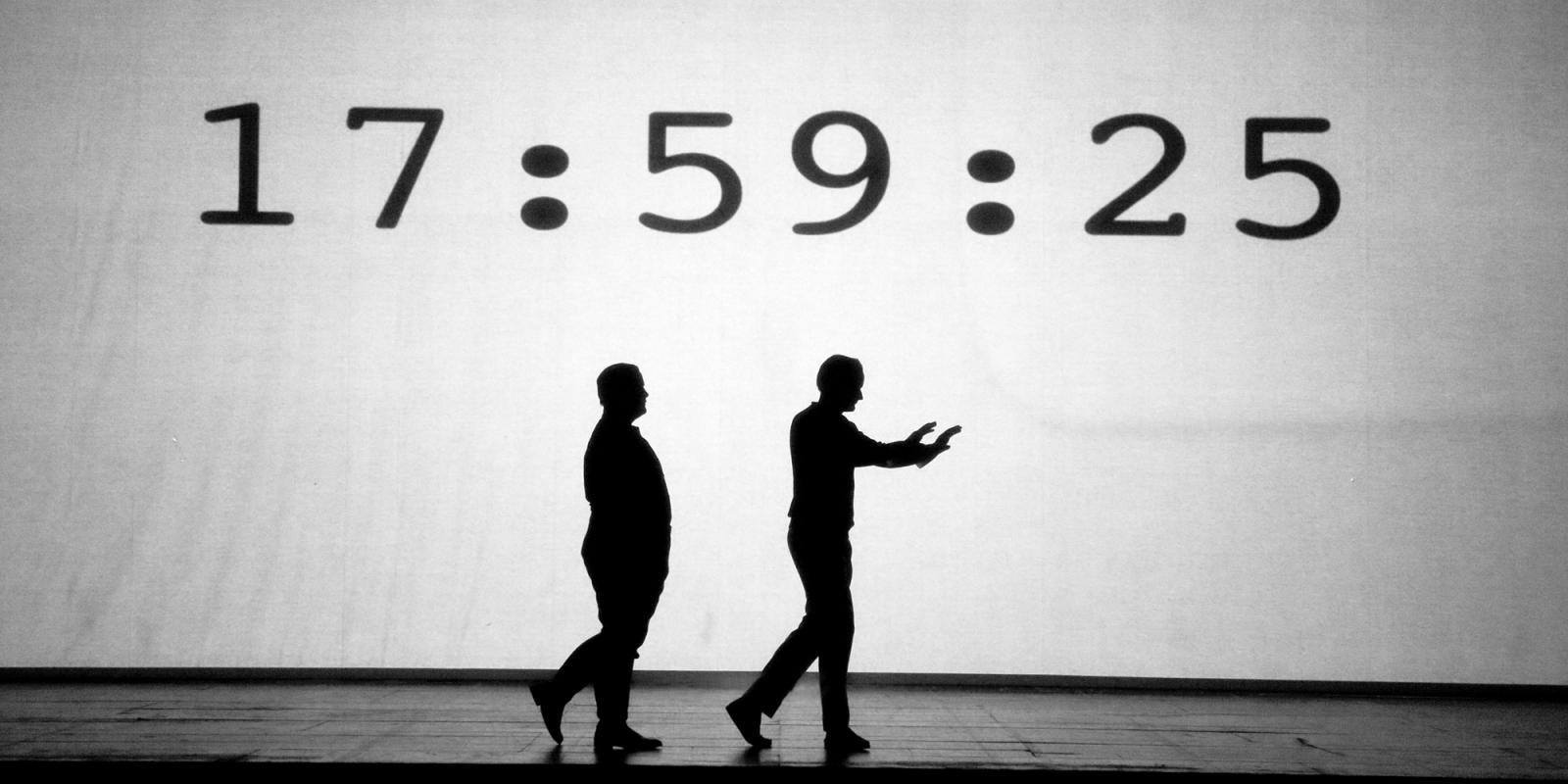 Orphée and Heurtebise walk silhouetted against a white background, with a bold timecode projected onto it.
