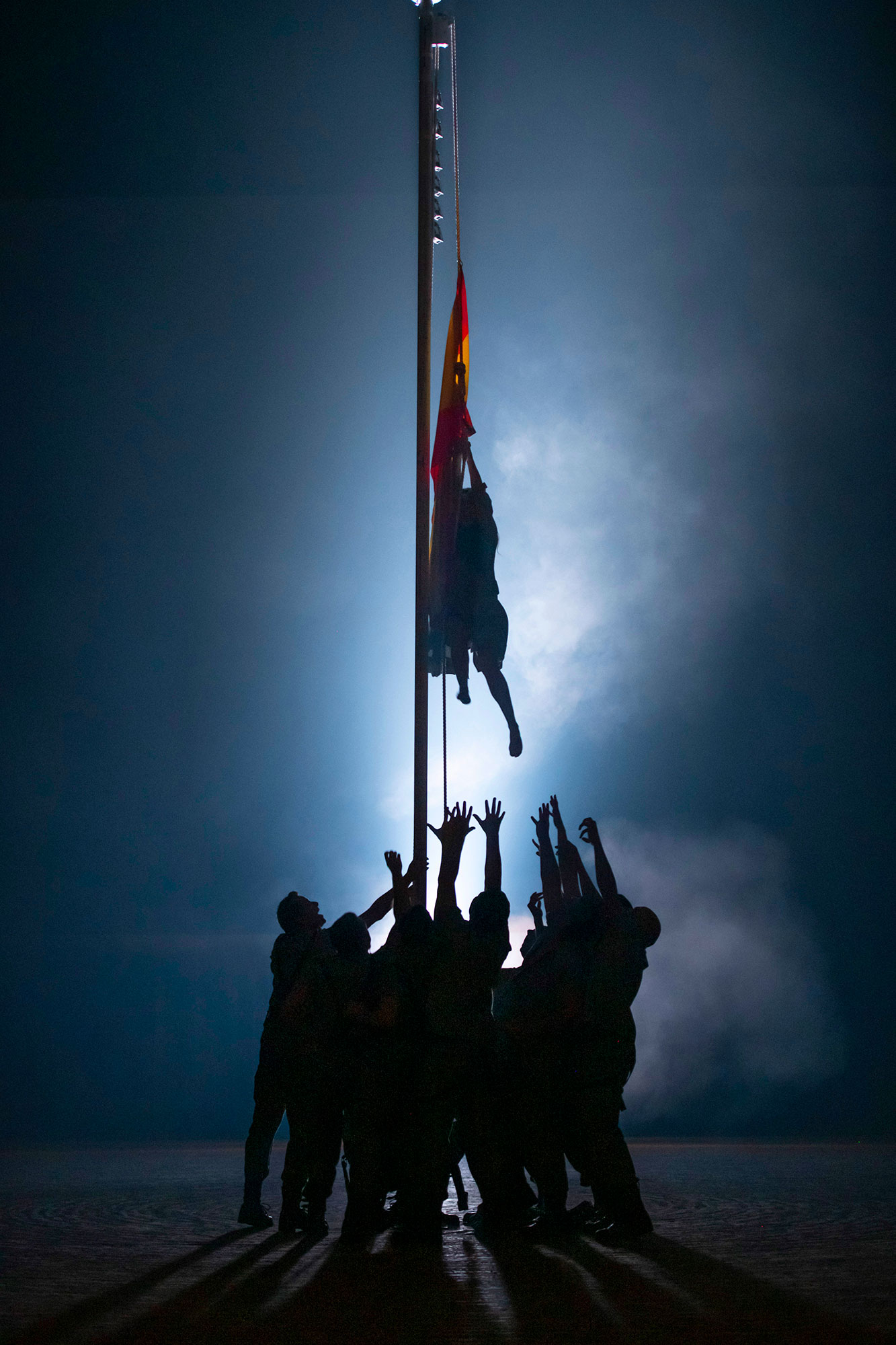 Silhouetted group stand around a flagpole, reaching up for the Spanish flag